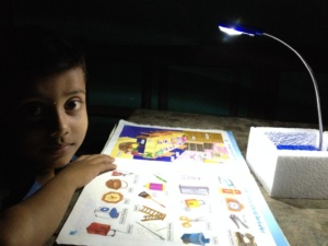 Child Reading With A Solar Lamp